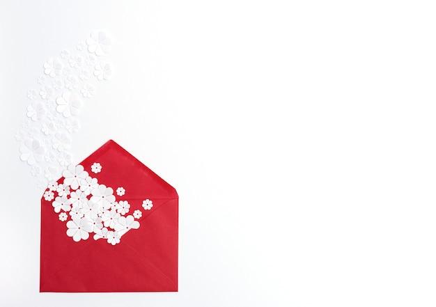 Envelope vermelho com flores de papel branco em fundo branco com espaço de cópia