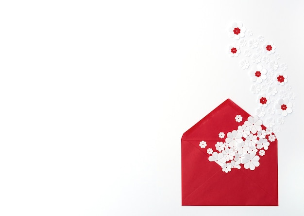 Envelope vermelho com flores de papel branco sobre fundo branco cartão de saudação ou convite plano