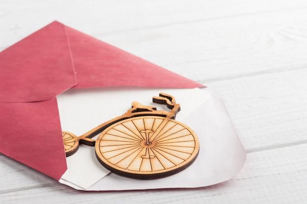 Envelope vermelho com papel vazio e bicicleta de madeira