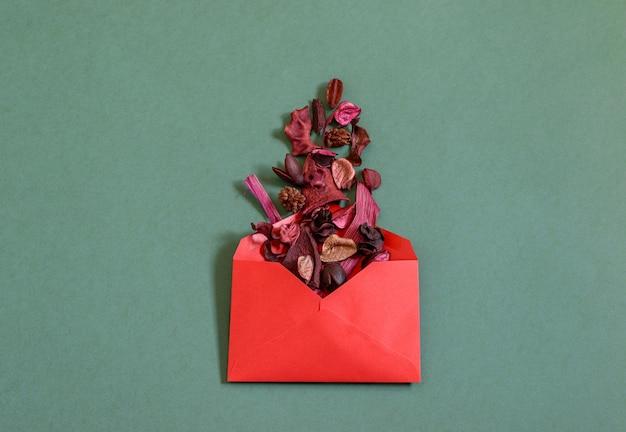 Envelope vermelho com pétalas de rosa secas sobre fundo verde.