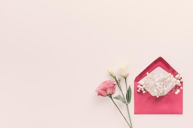Envelope vermelho com ramos de flores na mesa