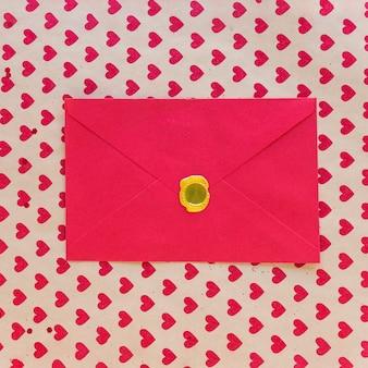 Envelope vermelho na mesa com padrão de corações