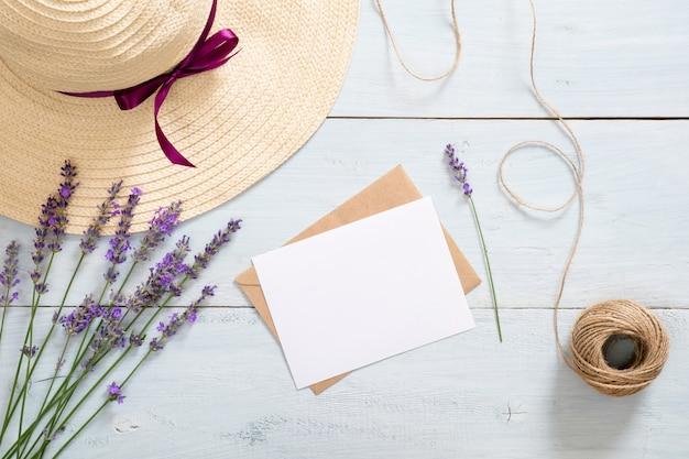 Envelope vintage, maquete de cartão de papel em branco, flores de lavanda, chapéu de palha e barbante