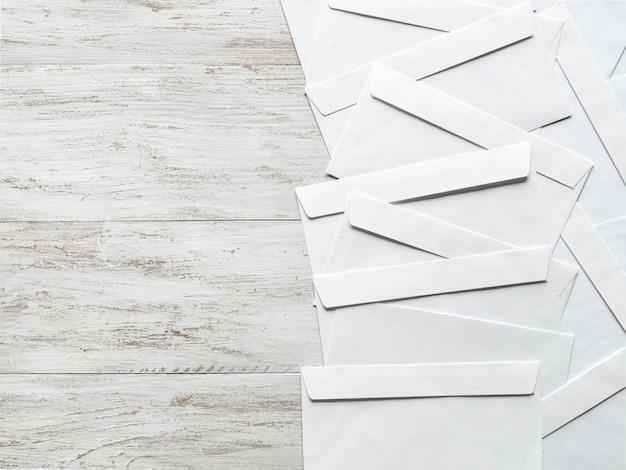 Envelopes brancos são dispostos em uma mesa de madeira