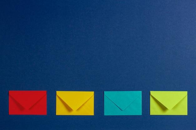 Envelopes coloridos na vista superior do plano de fundo azul