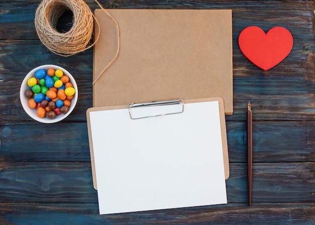 Envelopes de artesanato vazio e folha para caligrafia, corda, doce, caneta de tinta, coração vermelho sobre fundo de madeira