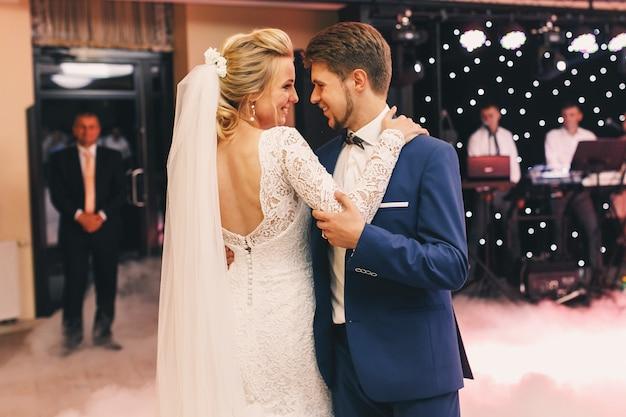 Envelopes de fumo branco feliz casal de noivos dançando no hall