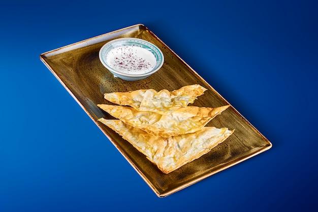 Envelopes de massa fina com recheio de queijo salgado e molho de natas em um prato verde. massa de pão saboroso. chebureks com queijo