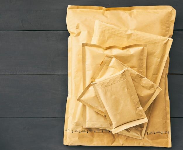 Envelopes de papel de diferentes tamanhos na mesa de madeira