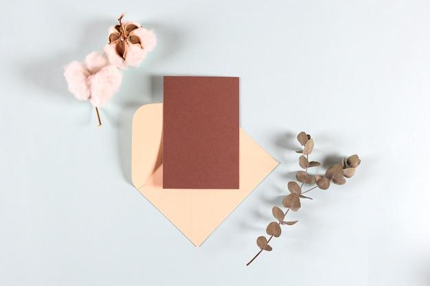 Envelopes de papel kraft em branco, cartas para correspondência com folhas de eucalipto e flores de algodão
