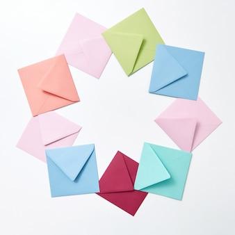 Envelopes hndcraft coloridos vazios em forma de moldura redonda sobre um fundo cinza claro com espaço de cópia.