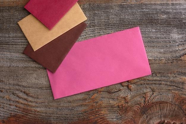 Envelopes multicoloridos em um fundo de madeira. ð¡omunicação ñ oncept.