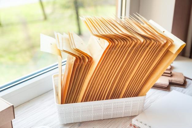 Envelopes postais marrons na mesa de escritório de madeira, área de trabalho