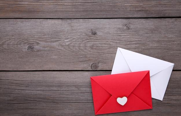 Envelopes vermelhos e brancos em fundo cinza