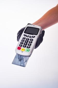 Envia um terminal de pagamento. mãos com luvas.