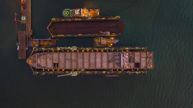 Envie na opinião aérea do estaleiro, navio na doca seca de flutuação sob o reparo limpando com jato de areia e pintando no estaleiro.
