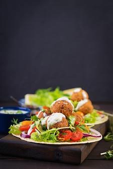 Envoltório da tortilha com falafel e salada fresca.