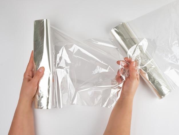 Envoltório de alimento plástico para assar produtos no forno na mão das mulheres