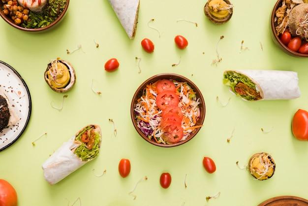 Envoltório do burrito; tomates cereja e saladeira em pano de fundo verde hortelã