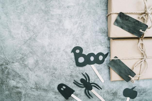 Envoltórios com rótulos escuros feitos à mão deitados ao lado dos atributos do dia das bruxas
