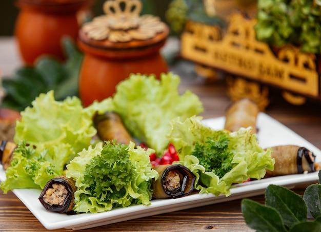 Envoltórios de beringela com carne moída e ervas servidas com folhas de alface