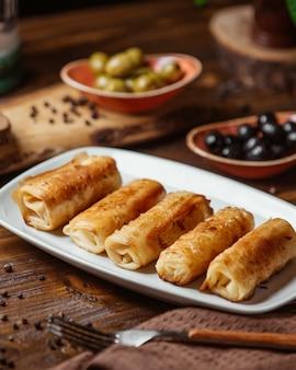 Envoltórios de carne frita como acompanhamento para jantar com azeitonas