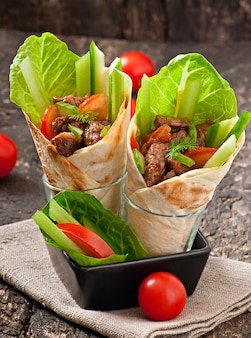 Envoltórios de tortilha com carne e legumes frescos