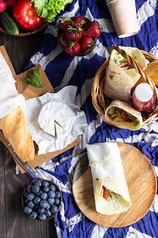 Envoltórios de tortilha com frango assado e legumes, sucos frescos, legumes e frutas diversas, baguete e queijo