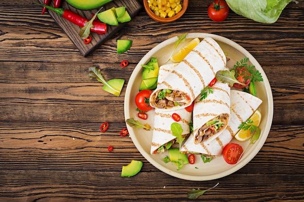 Envoltórios dos burritos com carne e vegetais em um fundo de madeira. burrito de carne, foo mexicano