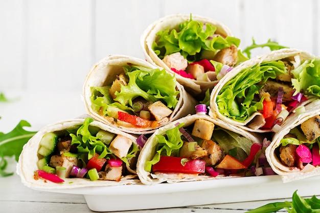 Envoltórios mexicanos da tortilha do fajita da comida da rua com a faixa grelhada da galinha e os legumes frescos.