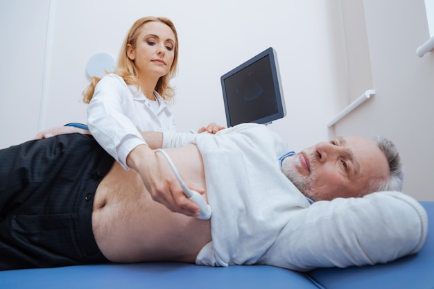 Envolvida médica alegre trabalhando no hospital, fornecendo monitoramento corporal por ultrassom e usando máquina de ultrassom