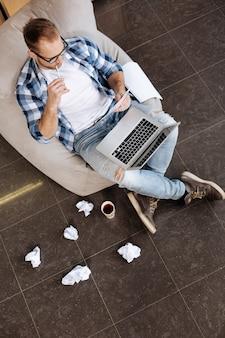Envolvido no trabalho. vista superior de um bom homem autônomo pensativo sentado na poltrona e mordendo a caneta enquanto lê algumas anotações