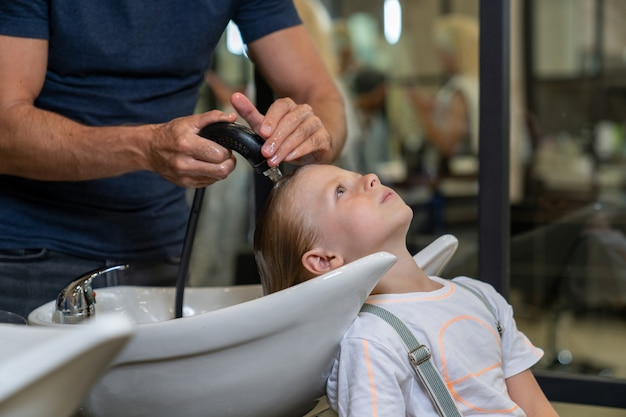 Enxágue a cabeça do menino após a lavagem antes de cortar