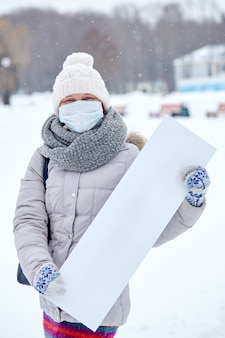 Epidemia do coronavírus. mulher em uma máscara protetora com uma placa