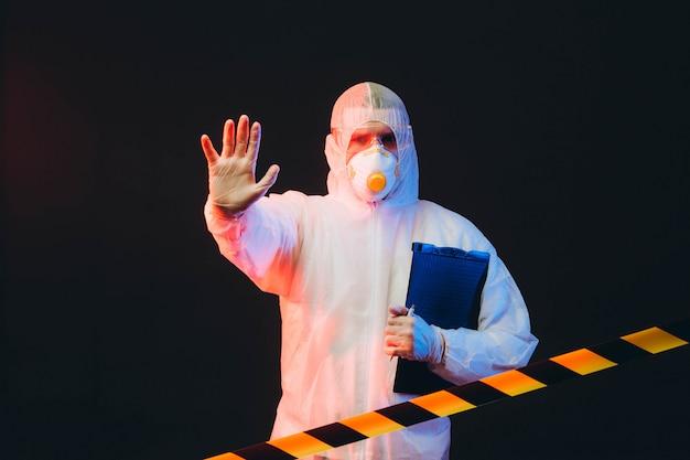 Epidemiologista em roupas de proteção em área restrita, fazendo um gesto de negação