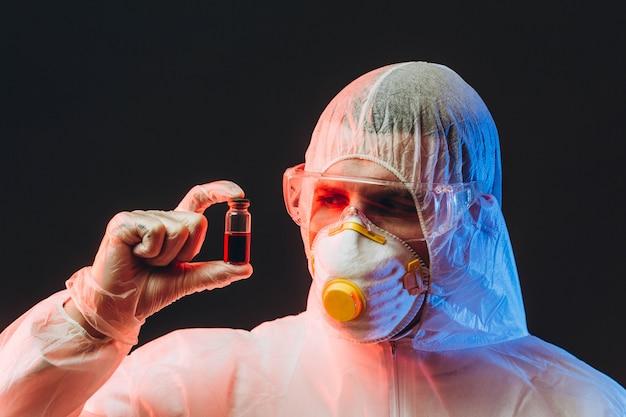 Epidemiologista em roupas de proteção em área restrita, segurando um tubo de ensaio