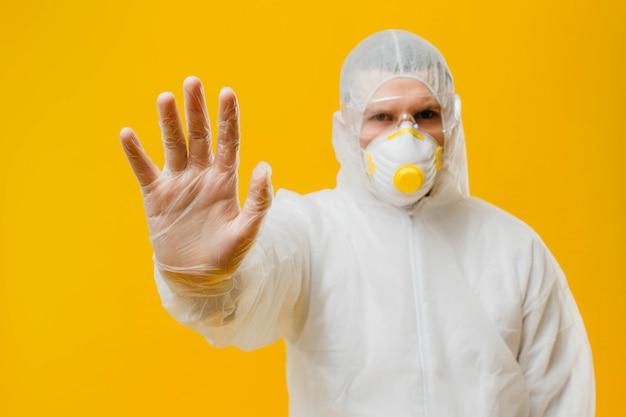 Epidemiologista em um terno de máscara e hazmat na parede amarela, fazendo um gesto de negação