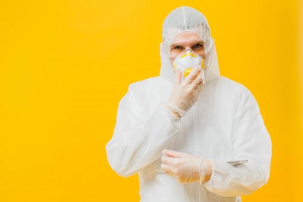 Epidemiologista em um terno de máscara e hazmat na parede amarela
