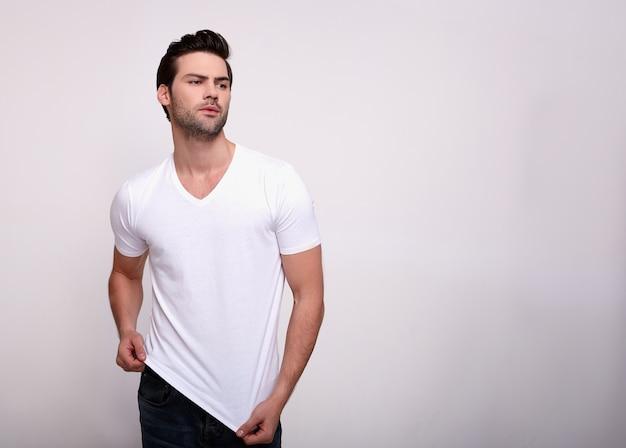 Epítome da masculinidade. o homem considerável mostra fora seu corpo perfeito que olha afastado, isolado sobre o branco.