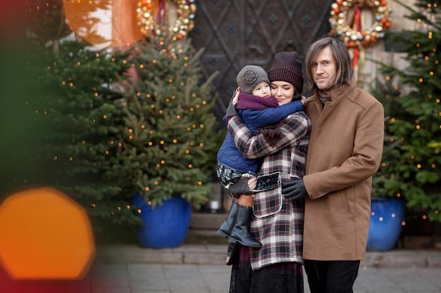 Época de natal. família feliz - mãe, pai e filha andando na cidade e se divertindo.