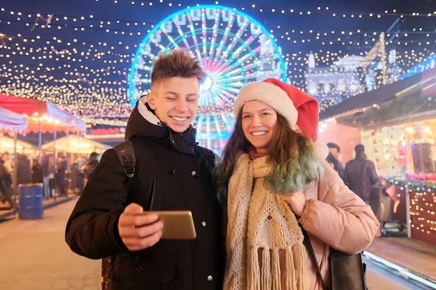 Época de natal, feriados de ano novo. jovens, casal de adolescentes se divertindo no mercado de natal