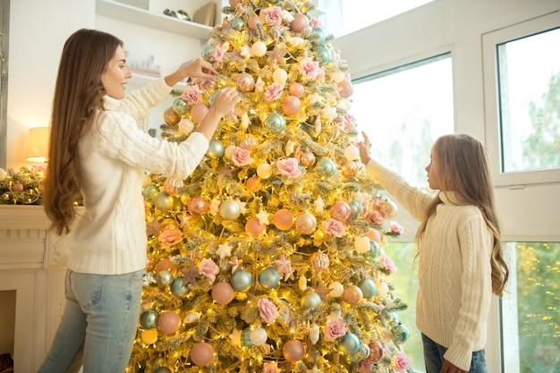 Época de natal. mãe e filha decorando árvore de natal em casa