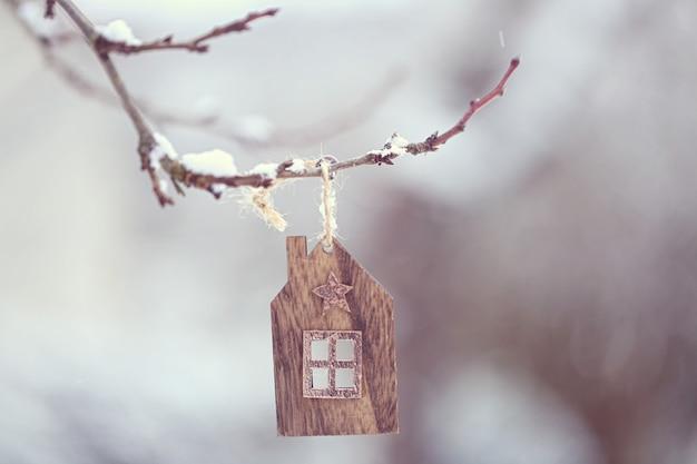 Época de natal. uma pequena casa de madeira balança em um galho e grandes flocos de neve caem devagar.
