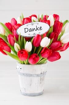 Época de primavera. buquê de tulipa vermelha no branco de madeira.