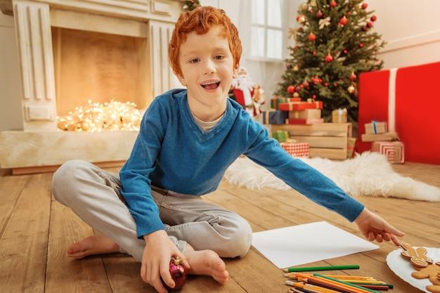 Época favorita do ano. garoto ruivo extremamente feliz com os olhos cheios de emoção enquanto leva um boneco de gengibre e aproveita as férias de natal em casa.