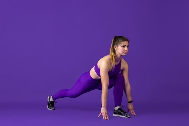 Equilibrado. bela jovem atleta praticando, retrato roxo monocromático. treinamento esportivo modelo de ajuste caucasiano. musculação, estilo de vida saudável, conceito de beleza e ação.