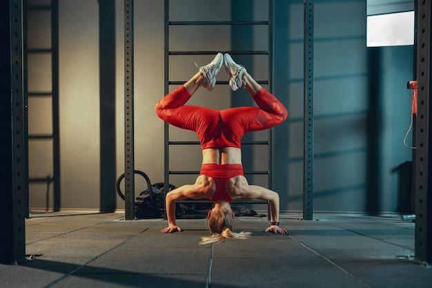 Equilibrado. jovem mulher caucasiana muscular praticando no ginásio. modelo feminino atlético fazendo exercícios de força, treinando sua parte inferior, parte superior do corpo, alongamento. bem-estar, estilo de vida saudável, musculação.