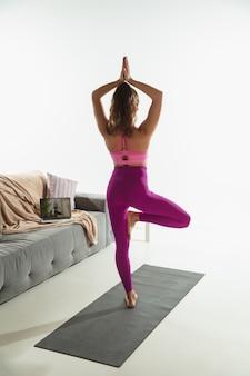 Equilibrado. mulher jovem e bonita malhando dentro de casa, fazendo exercícios de ioga na esteira cinza em casa. cabelo comprido apto praticando modelo caucasiano. conceito de estilo de vida saudável, mental, atenção plena, equilíbrio.