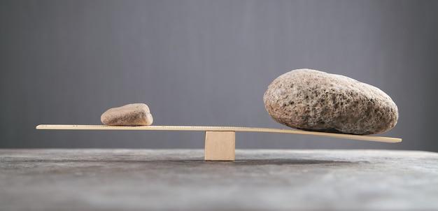 Equilibre pedras em balanças de madeira.