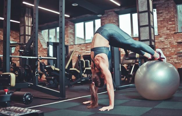 Equilíbrio, conceito de força. mulher desportiva de cabeça pra baixo com as pernas na bola de forma. menina no treinamento de sportswear na fitball no ginásio. esporte, treinamento físico